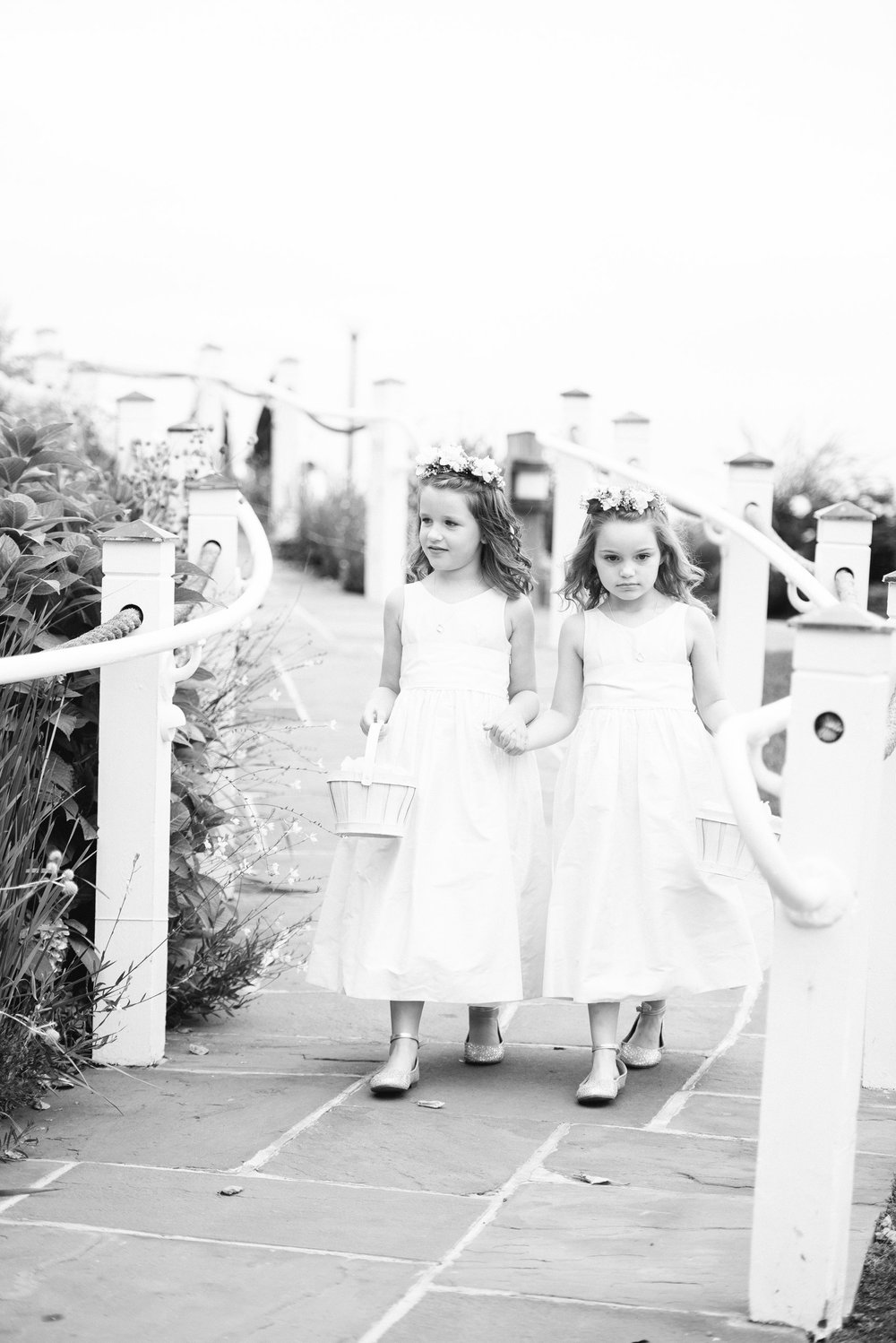 flower girls wearing flower crowns and carrying flowers by green of greenwich