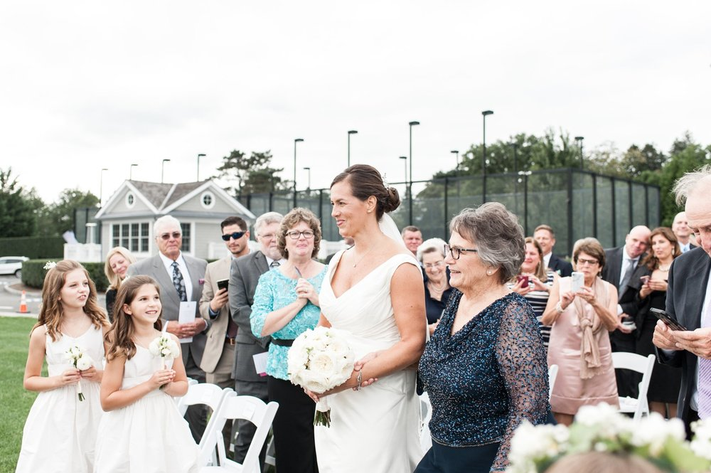 escorted by mom down the aisle to groom at fall wedding at belle haven club