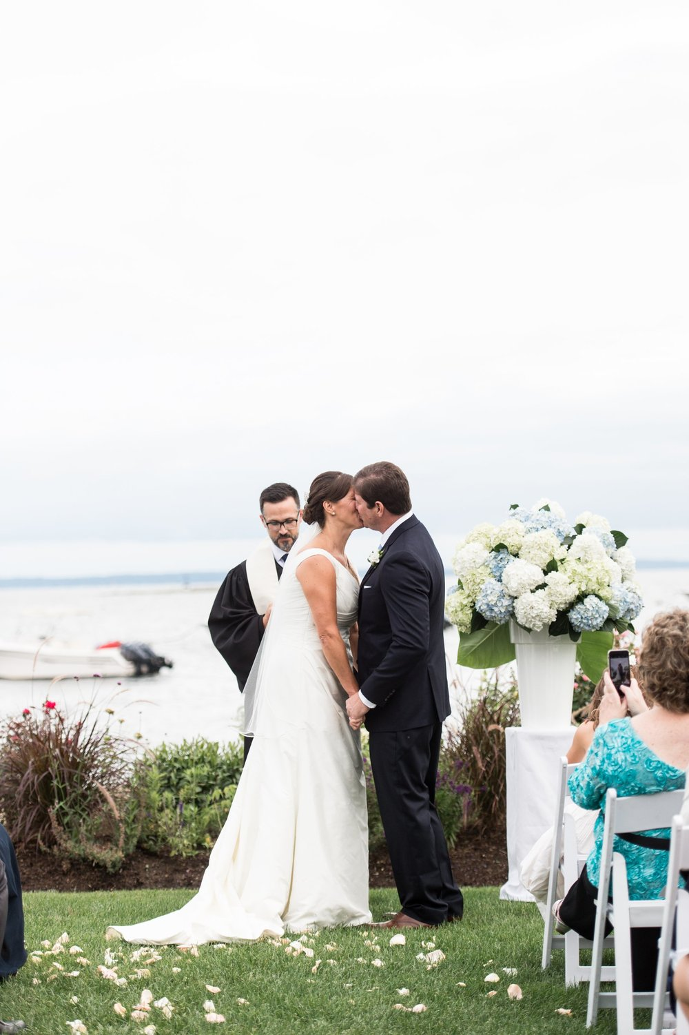 first kiss by bride and groom at wedding ceremony at Belle Haven Club in Greenwich CT