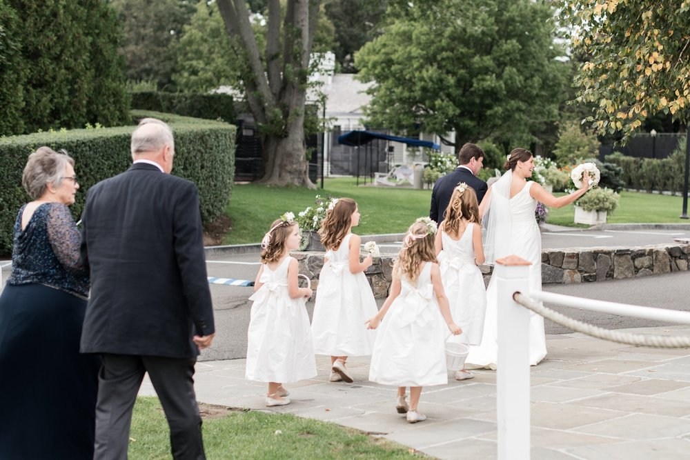 newlyweds and flower girls in white jcrew dresses exiting ceremony at Belle Haven Club