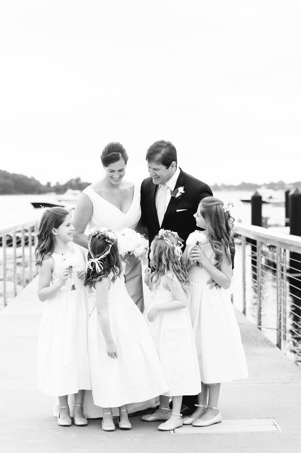 Bride and Groom in Augusta Jones dress with four little flower girls in white jcrew dresses pose on docks at Belle Haven Club for fall nautical inspired wedding