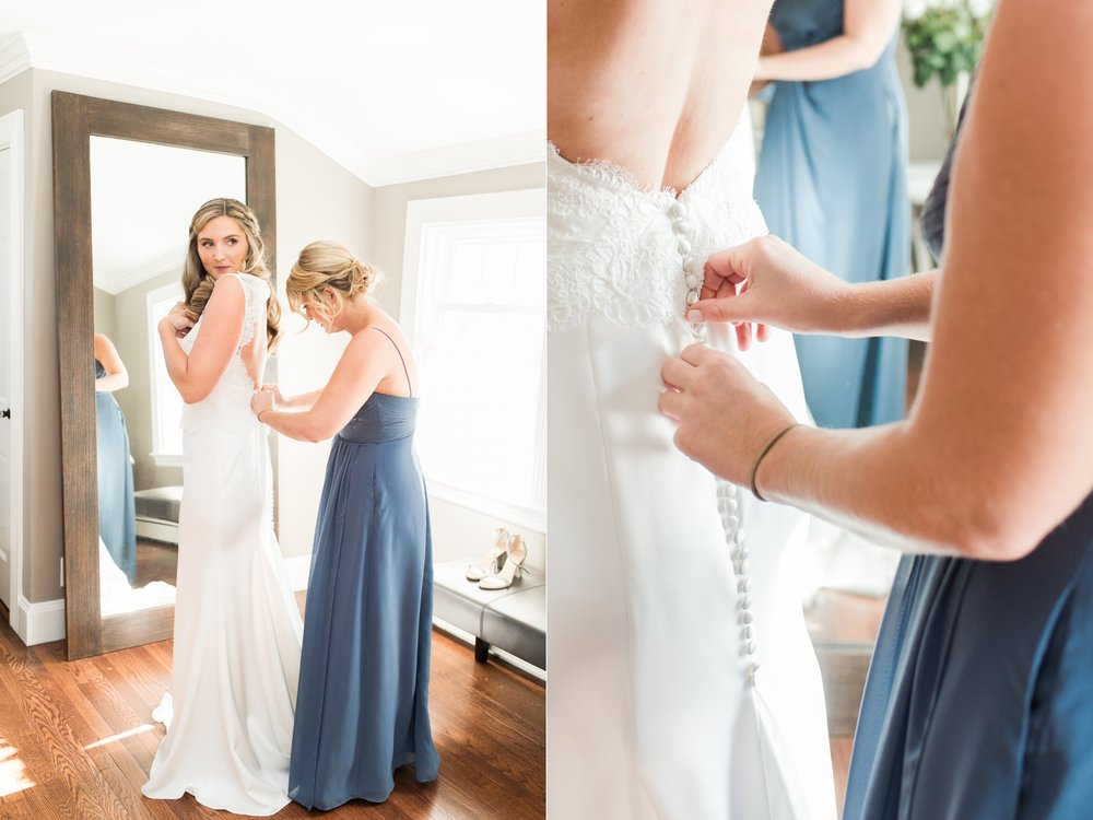 Bride putting on bridal gown in bridal suite with bridesmaids in dusty blue dresses The Dennis Inn Cape Cod Wedding