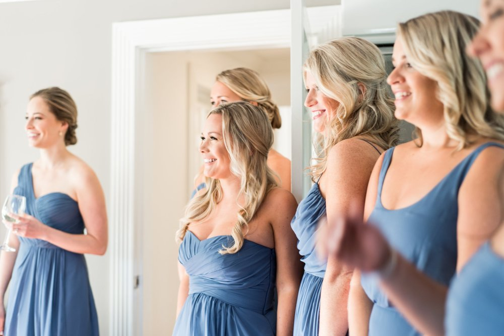bridesmaids in dusty blue full length dresses styled one shoulder off the shoulder strapless with pockets