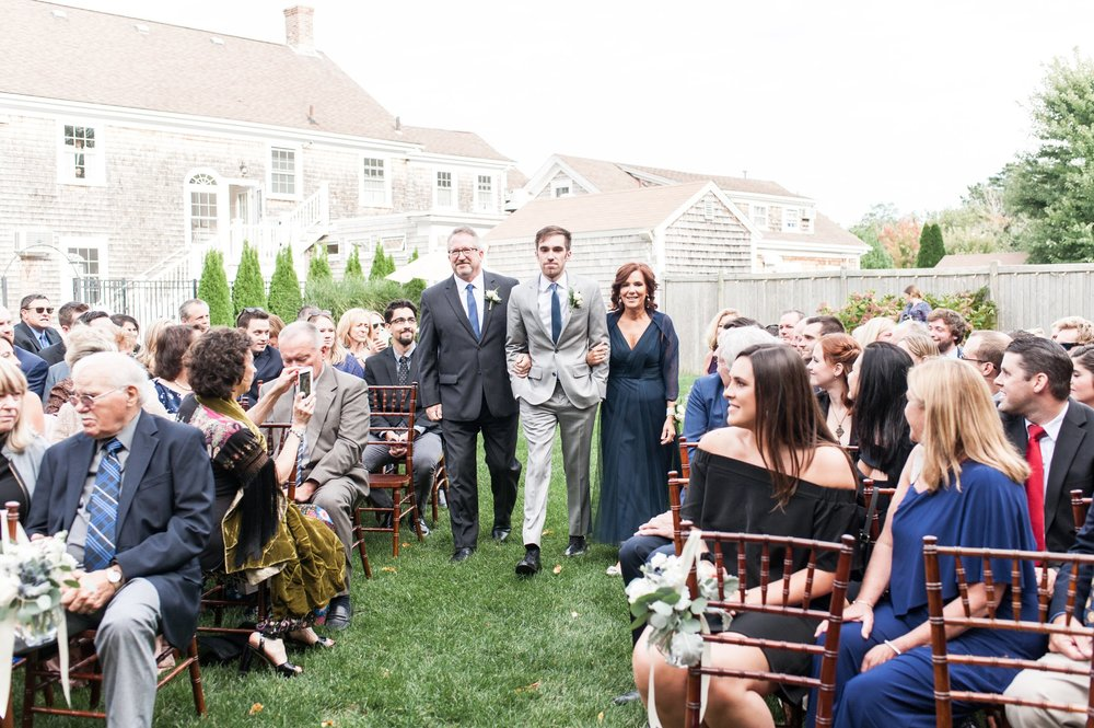 Groom walked down the aisle by mom and dad at back yard outdoor wedding ceremony at the Dennis Inn