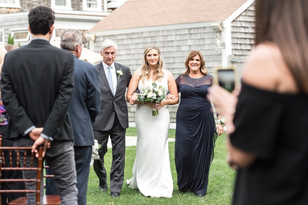 Bride walked down the aisle by Mom and dad at back yard outdoor wedding ceremony at the Dennis Inn