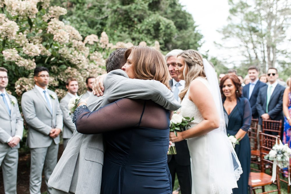 groom hugs mother in law as she gives her daughter away at cape cod wedding