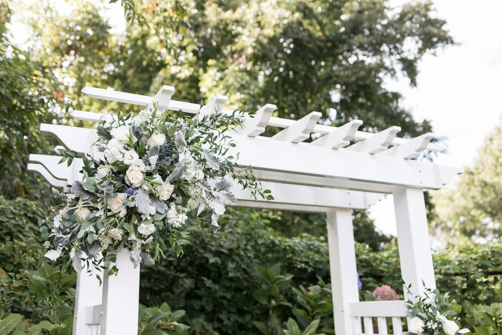 Backyard ceremony with pergola Ceremony floral inspiration and decor by Designers Touch Florals at the Dennis Inn for a Cape Cod Wedding