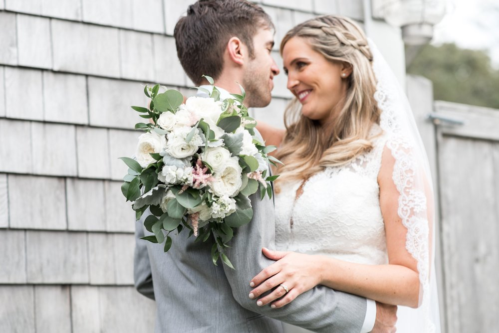 classic cape cod wedding portraits of bride and groom at the dennis inn with wood shingle sided house