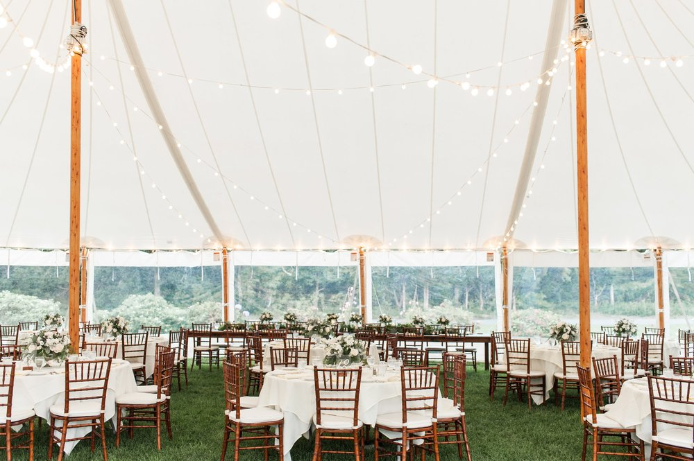 tented wedding reception decor bistro lights lush green table runners and white floral centerpieces with menu cards