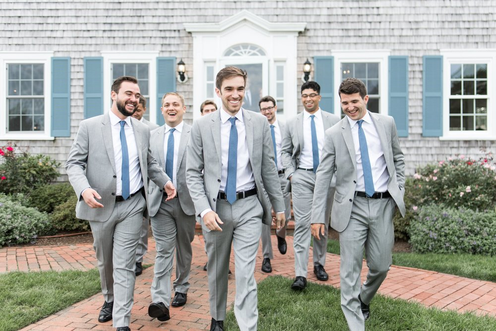 groomsmen in gray suits with blue ties pose with groom for portraits at the Dennis Inn at Cape Cod Wedding