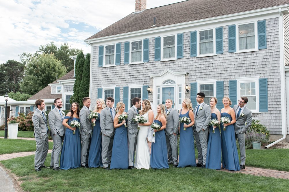 bridesmaids in dusty blue groomsmen in gray suits with blue ties pose with bride and groom for portraits at the Dennis Inn at Cape Cod Wedding