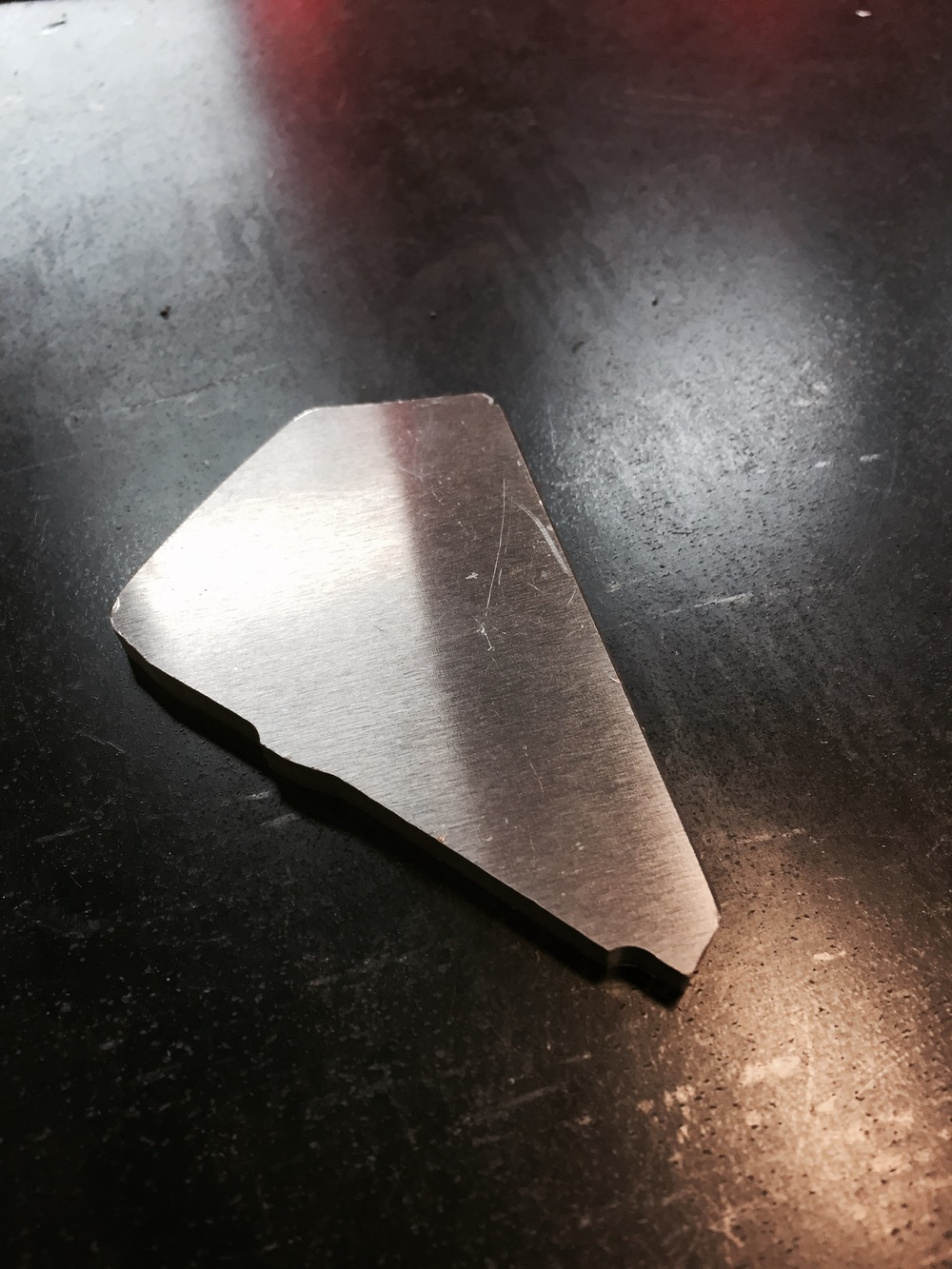 "The gusset is a 3/16"" thick 5052 aluminum part that is also cut on the CNC Router.  The little tab sticking down seems like it is cut on an odd angle; however, much thought was put into the shape of it.  The Robot Cell Operator can easily slide each gusset into place, but they will not fall out when the entire assembly rotates in the robotic jig."