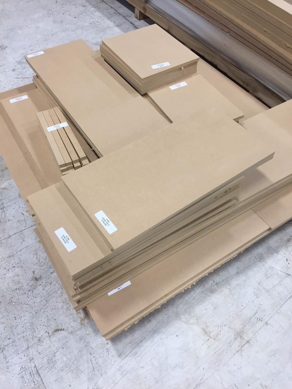 Stacks of consistent and accurate parts on a pallet ready to ship.  Notice each one has a label with the part number, thickness, and dimensions.