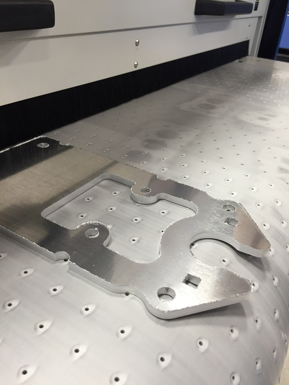 Here is an aluminum laser cut part about to be fed into the machine.  Laser cutting aluminum usually leaves a burr all of the way around the cut edges.  A part such as this could take someone approximately 2 minutes to debur properly. The small holes you see in the conveyor are actually vacuum ports which help to hold the part in place while the brushes do their work.