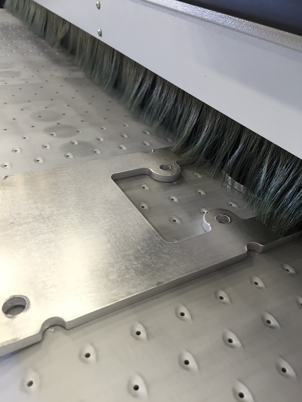 The finished part exiting the machine is completely free of burrs and sharp edges. You'll also notice the large surface of the part has received a slight brushed finish which helps eliminate small scratches on the surface of the part.