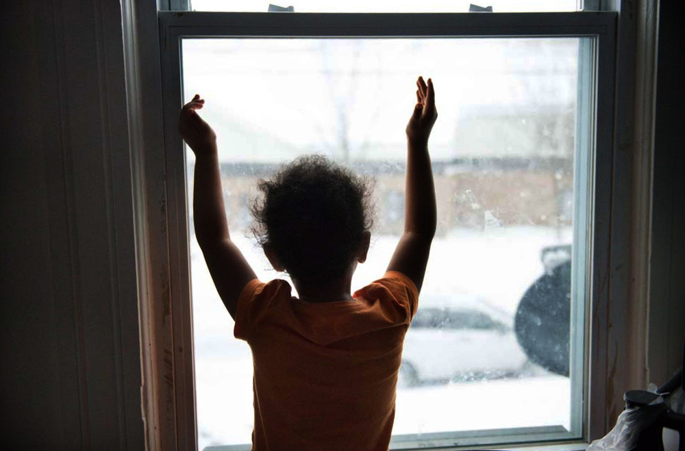 Lydianyz Huertas, 5, daughter of Lydia Huertas, watches snow fall from her bedroom window in Syracuse.