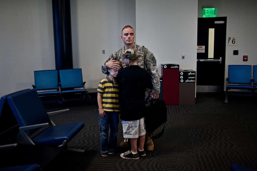 As the departure gate empties out into the boarding plane, Sergeant First Class Brian Eisch says goodbye to both his sons with a quiet embrace.