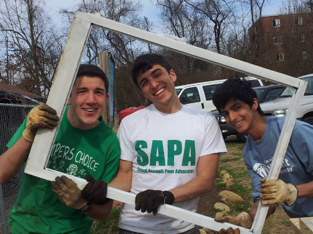 IMAGE DESCRIPTION:  Three teenagers wearing gardening gloves smiling at the camera through an old white poster frame.