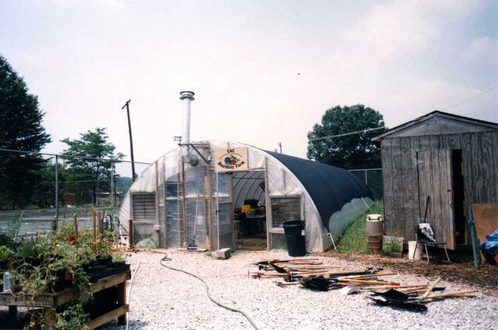 "IMAGE DESCRIPTION:  A fenced-in area. In the center of the photo along the fence is a greenhouse with a sign that says ""CAC BEARDSLEY FARM."" To the right of the greenhouse is a wooden shed with the door slightly ajar. To the left of the greenhouse are some garden beds."