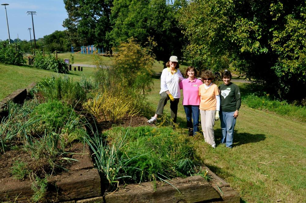 IMAGE DESCRIPTION:  Four people are seen standing next to the herb beds at Beardsley Farm.
