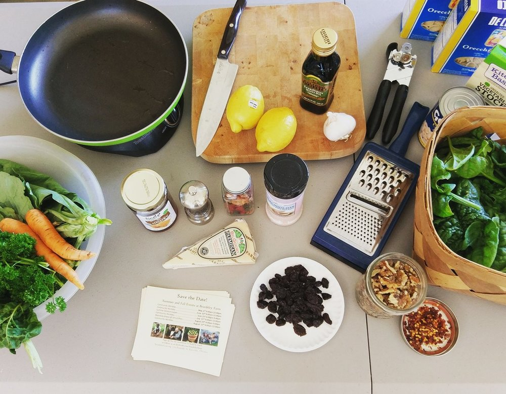 IMAGE DESCRIPTION:  An above shot of the prep for a cooking demonstration. We can see various kitchen utensils like knives, pans, and a cheese grater, along with fresh produce, cheese, and various spices.