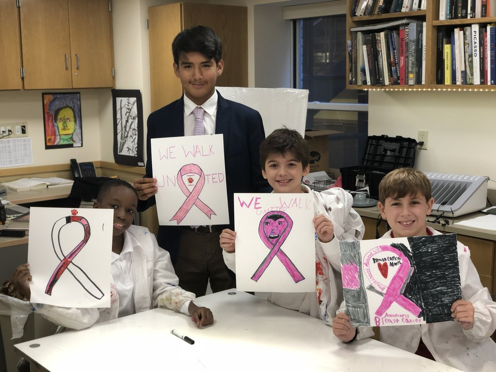 Fourth graders make signs in support of Breast Cancer Awareness Week in art class with members of the varsity soccer team.