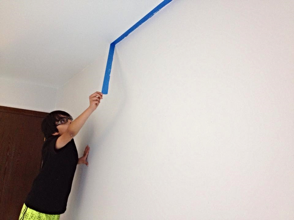 Taping off a room before painting helps create a straight edge between two different colors. Since the wall is now dry, Danny pulls the tape down and inspects the work!