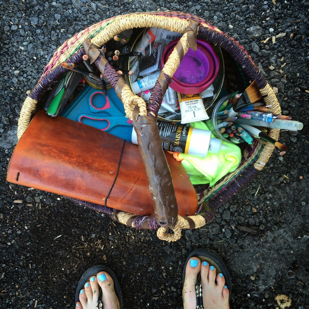 My art basket: a portable studio I use when I go on vacation.  A great option for someone with limited art making space at home.   Supplies pictured: traveler's notebook, rags, glue, scissors, old book I am cutting apart for collage elements, a collaborative journal to work on,  jars of water-soluble pencils and graphite, tin of gouache tubes, brushes, water brush.