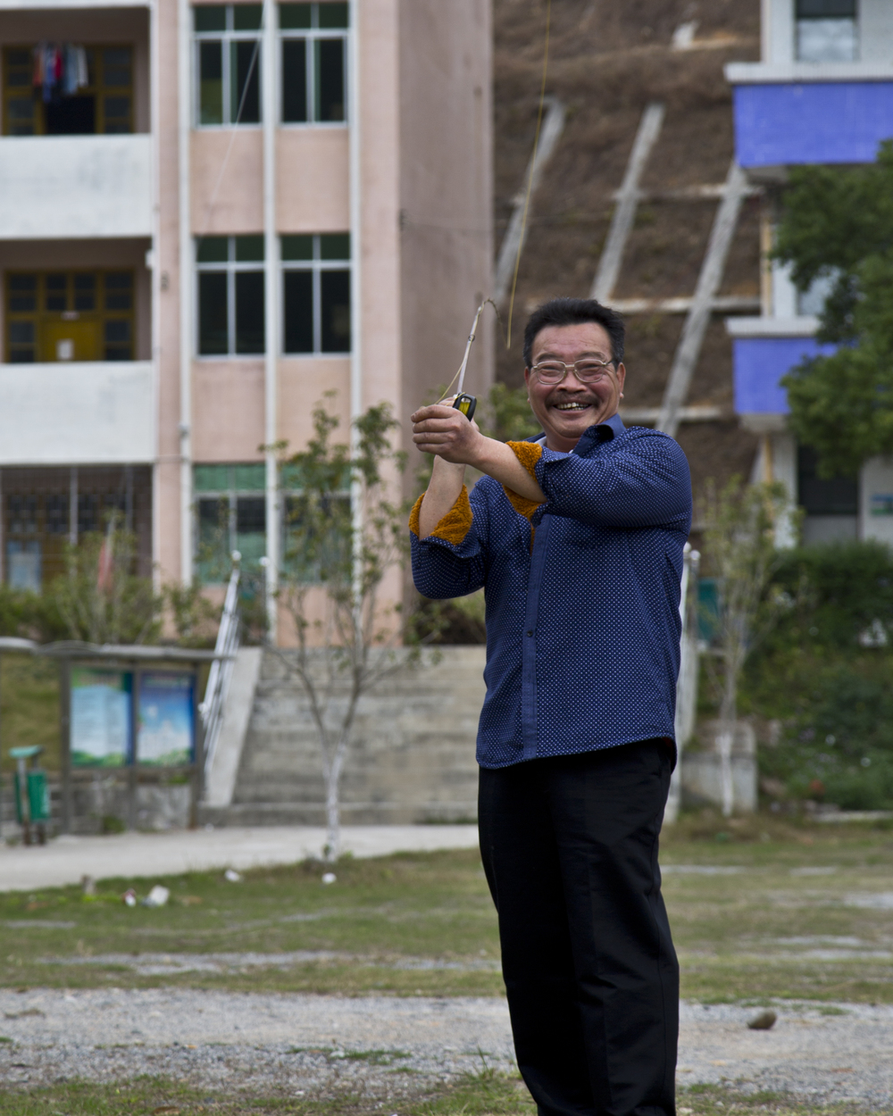 Lao Cai practicing the art of bamboo rod fly casting in the middle school playground across from his home.