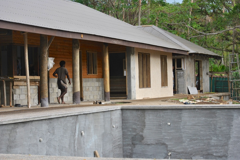 This is a great view of the entryway to the Salty Fox and the retail shop.  We love the contrast between the sand-aggregate finish and the wood siding.  The cinderblock will also be covered in sand aggregate.  In the background, you can see the utilities shed, which includes staff space, water closets, generators, and compressors. In the foreground is the very nice swimming pool.