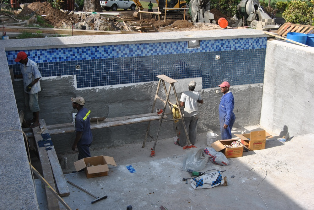 Craftsmen are working on the tiling the pool.  Man, is that a lot of tiles. You can also see the infinity edge to the right of the frame, and the polished concrete edge around the lip of the pool.