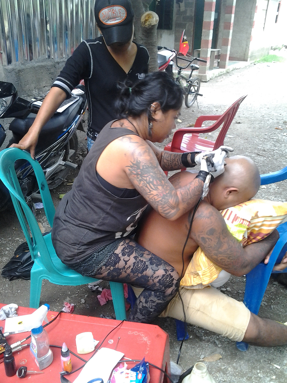 "Lenore ""Chaching"" Ankis Lay tattooing man's head, Kampuala. Photo Lenore Ankis Lay."