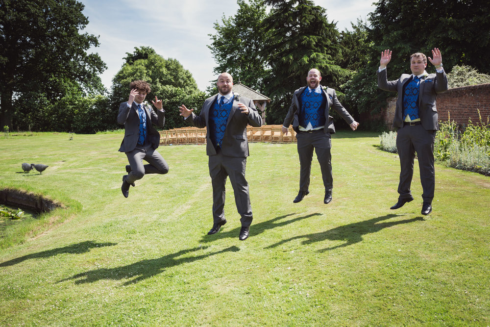Image of Paula & Martin's Groomsmen jumping in the air at Wedding at Great Lodge, Great Bardfield