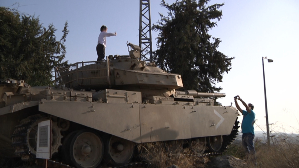 A father taking a picture of his son e outside the  Armored Corps Museum