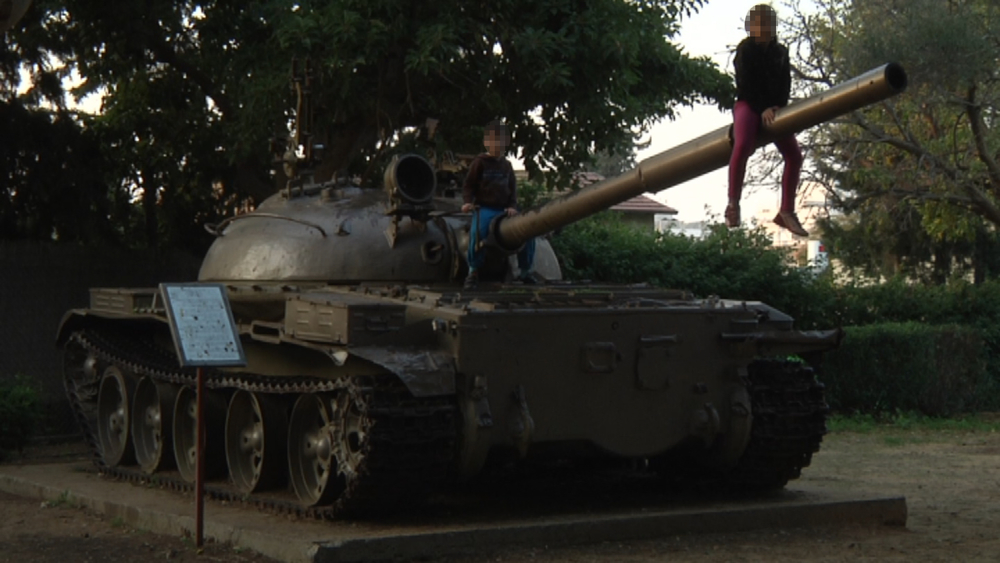 A tank standing in the middle of a park in a neighborhood in Petach Tikva