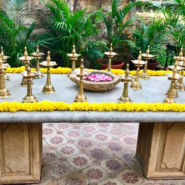 A stone table set with flowers and traditional brass oil lamps... #india #indianwedding #incredibleindia #southindianwedding #blooms #flowers