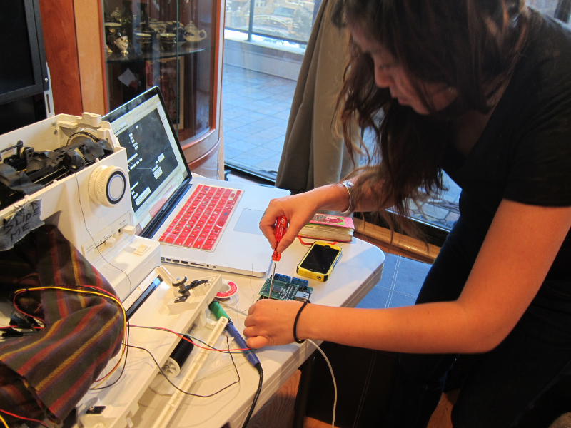 Betty connects sensors and wires to the sewing machine as she finalizes her installation