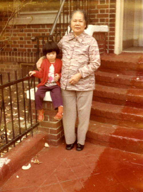 Artist Betty Yu with her grandmother in front of their Sunset Park home, circa 1981