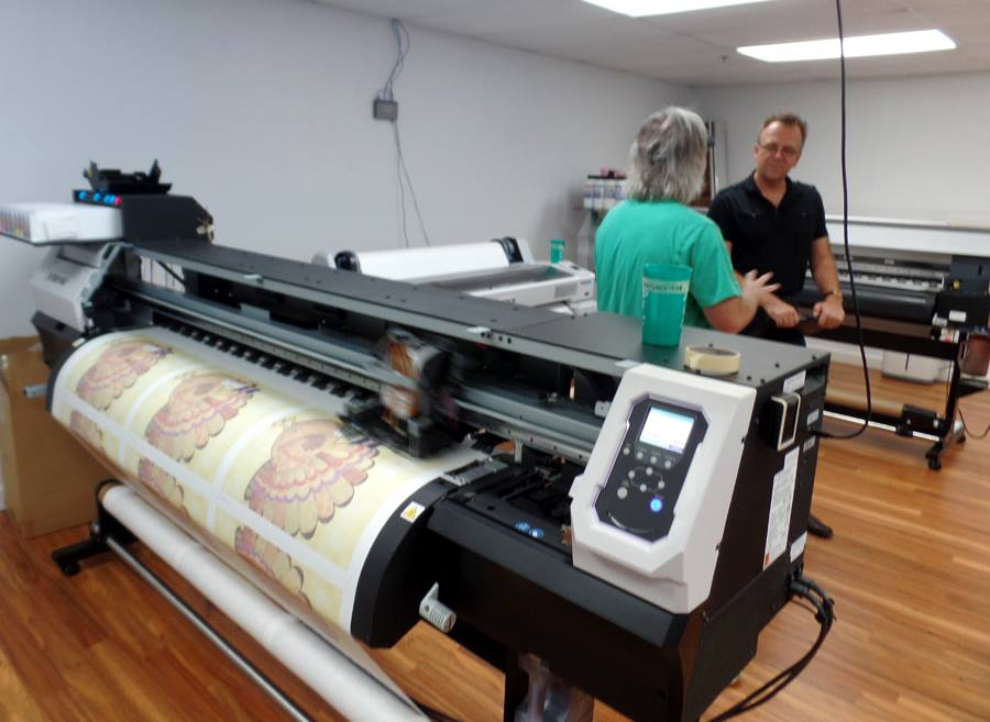 Hal Mortensen, director of production, and joe barsin, Citizen pride artist & owner, discuss new print technology for dye sublimation.