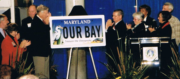 "Governor Harry Hughes of Maryland (left of plate) and the Chesapeake Bay Trust Board was on hand to unveil the new ""Treasure the Chesapeake"" plate."