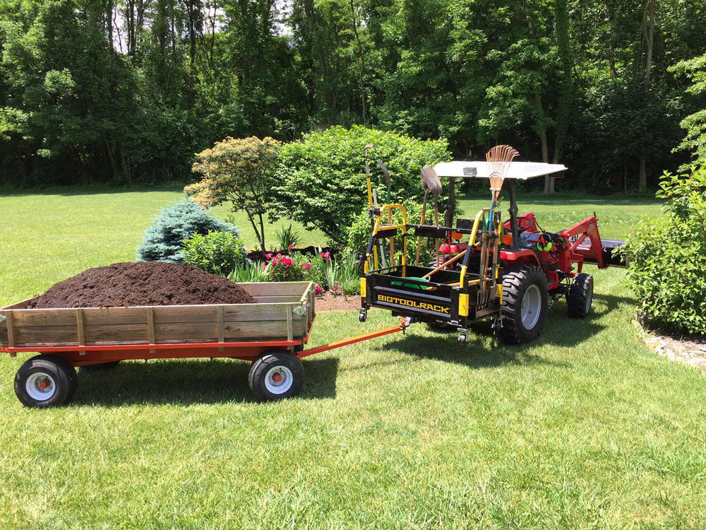 Bigtoolrack on Massey Ferguson towing a trailer and securely carrying many yard tools. The options are endless! BIGTOOLRACK turns your tractor into a pickup truck and more!!   It just makes sense!!!     GET MORE DONE WITH THE BIGTOOLRACK!