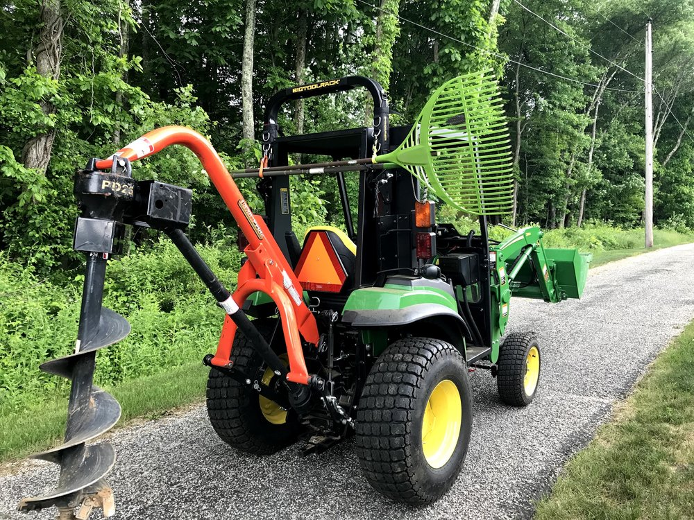 John Deere 2038R with the Bigtolrack ROPS Carryall and a land pride post hole digger