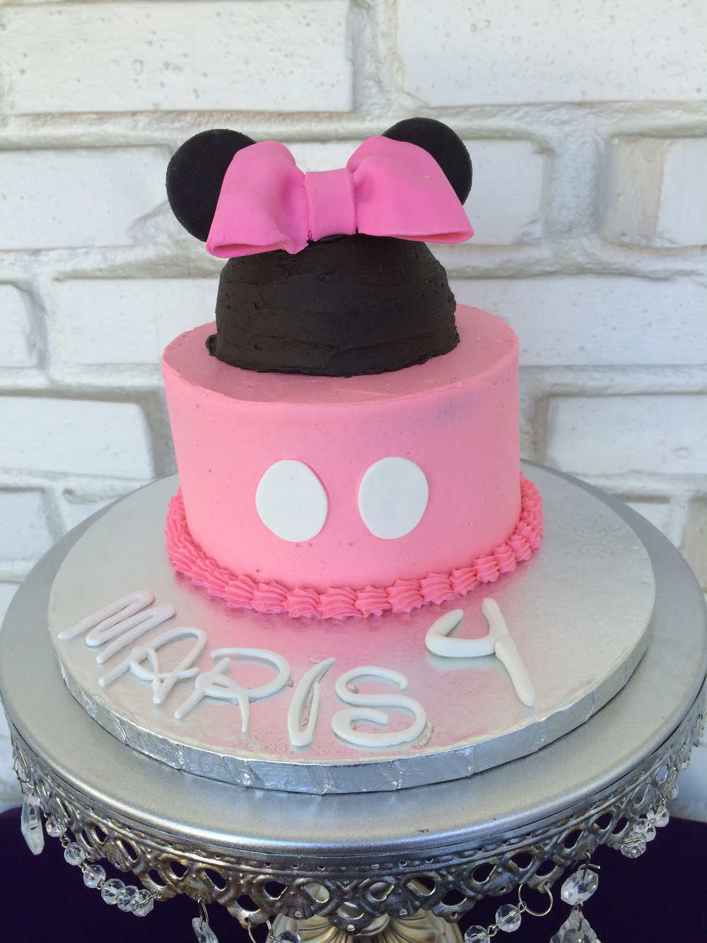 Chocolate cake filled with black cocoa buttercream and topped with vanilla buttercream and fondant accents