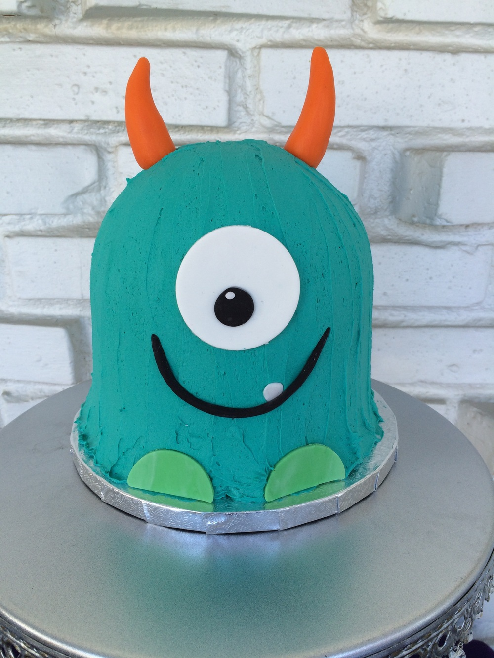 Lemon cake filled with lemon curd and topped with vanilla buttercream and fondant monster accents