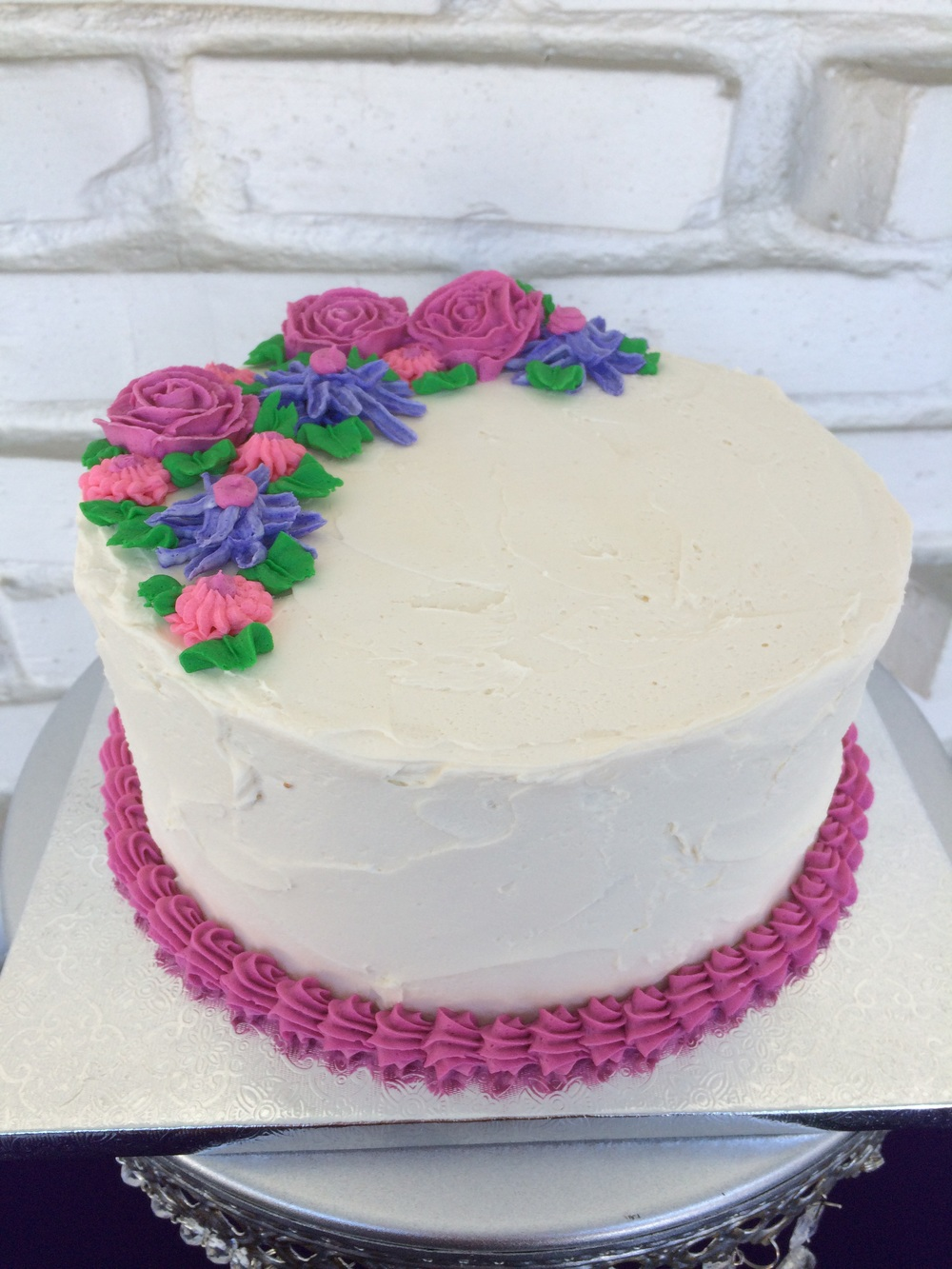 Lavender cake filled with creamed honey buttercream and adorned with buttercream flowers