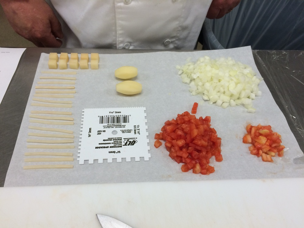 Knife cuts final exam with potatoes, onions and tomatoes