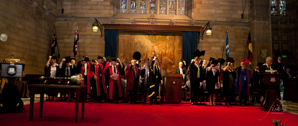 Members of the academic procession stand and salute the newest graduates. Image courtesy of the Dentistry Graduation Ceremony of 2011. (Ours had a little less bling).