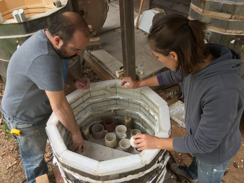 Jarad and Katie loading the kiln.  The shelves and pots are staggered to help create a flow for the flame and soda.