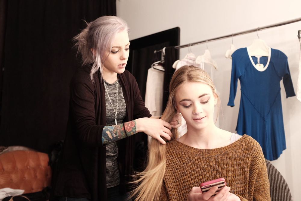 Kelly doing up a fishtail braid for Shannon's long-sweater look.
