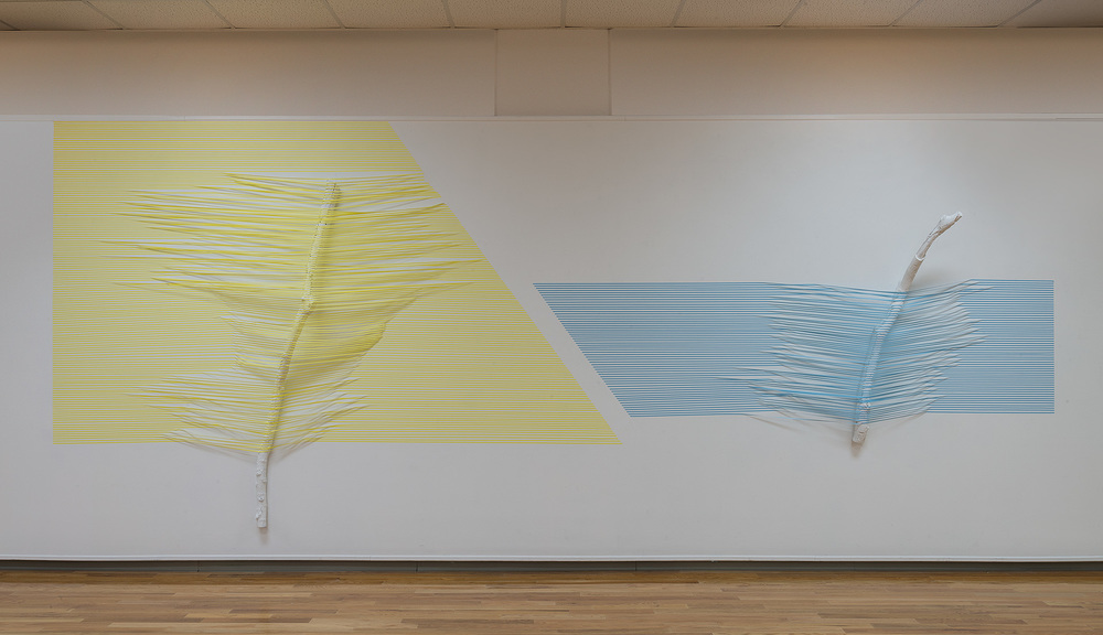 "Yellow and Blue Stick (40.0797 ° N,  88.2043 ° W)   2016  masking tape, paint and found sticks  96""  x  168""  x  10"""